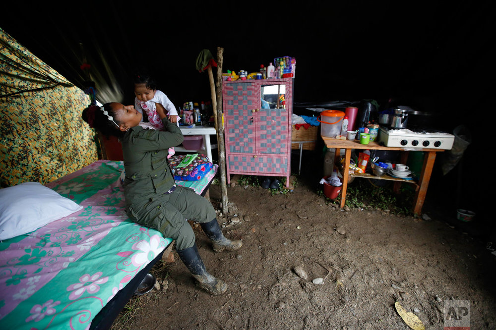 In this Tuesday, Feb. 28, 2017 photo, FARC rebel Sandra Saez plays with her 4-month-old daughter Manuela inside their tent at a rebel camp in a demobilization zone in La Carmelita, in Colombia's southwestern Putumayo state. The birth of babies at rebel camps and the arrival of older children who had been left with relatives during the conflict has injected a sense of optimism into camps where war-hardened rebels are beginning their transition to civilian life. (AP Photo/Fernando Vergara)