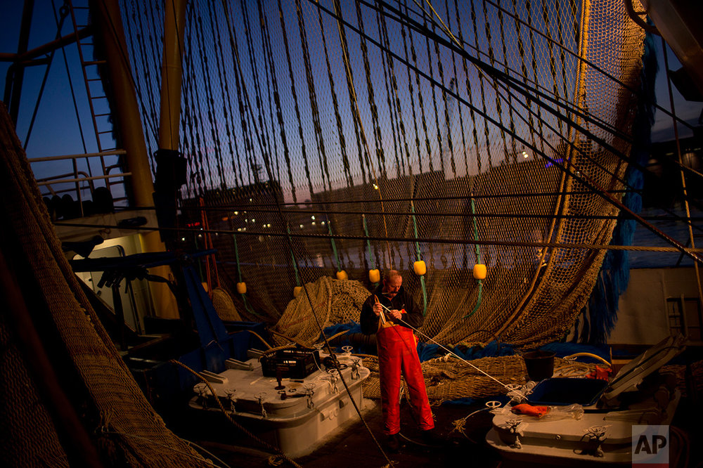 In this Friday, March 3, 2017 photo, a fisherman works on his ship fixing a fishing net at the port in The Hague, The Netherlands. (AP Photo/Emilio Morenatti)