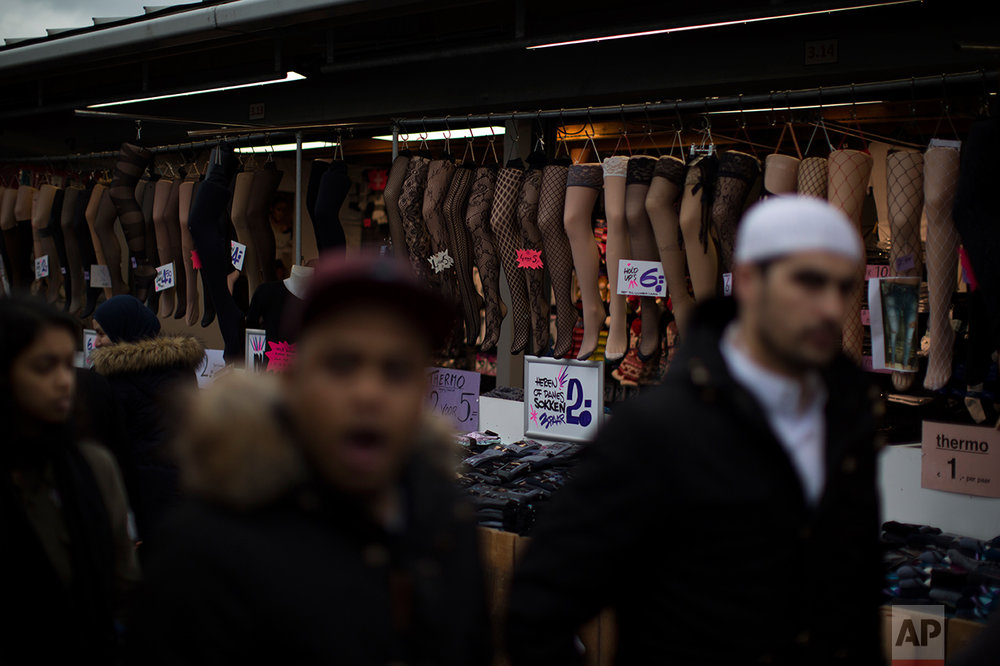 In this Saturday, March 4, 2017 photo, people walk past socks and stockings that are displayed for sale at a market stall in The Hague, The Netherlands. (AP Photo/Emilio Morenatti)