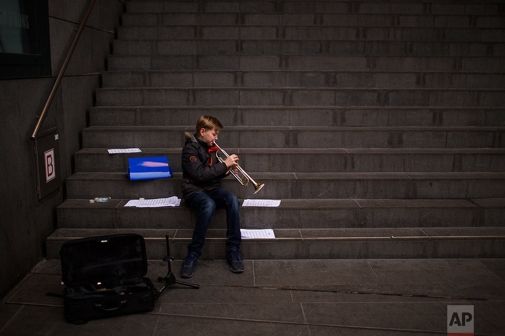 In this Friday, March 3, 2017 photo, Agne, 12, plays his trumpet as he practices in the centre of The Hague, The Netherlands. Of the Netherlands' 17 million people, just over one in five now have a migrant background _ rising to roughly half-and-half in the Netherlands' four largest melting-pot cities: Amsterdam, Rotterdam, Utrecht and The Hague. (AP Photo/Emilio Morenatti)