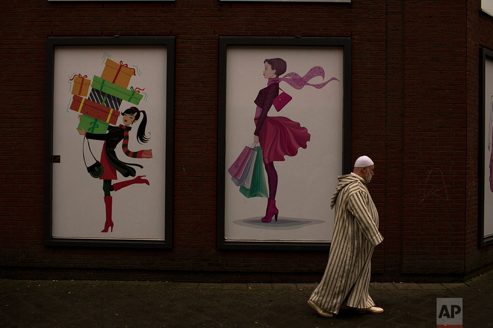 In this Friday, March 3, 2017 photo, a man walks past a clothes shop in the The Hague, The Netherlands. Islam is relatively new in the Netherlands and its spread has come as increasing numbers of native Dutch have abandoned religion. Those attending religious services at least once per month have dropped from about one in four in 1999 to about one in six now. (AP Photo/Emilio Morenatti)