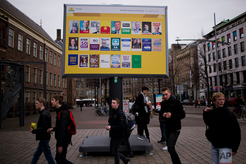 In this Friday, March 3, 2017 photo, people walk by a billboard showing the candidates for the Parliamentary elections scheduled for March 15 at The Hague, The Netherlands. Ahead of a Dutch vote that will indicate whether populism in Europe is gathering strength or blowing over, divisive questions about immigration and Islam are testing the Netherlands' famed capacity for tolerance and inclusiveness. (AP Photo/Emilio Morenatti)