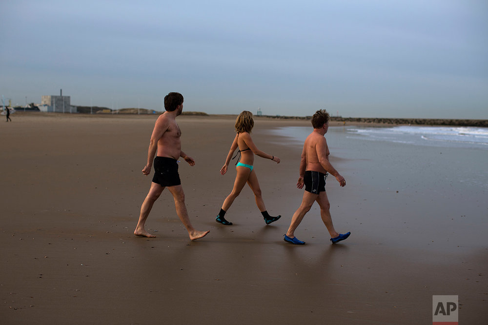 "In this Friday, March 3, 2017 photo, Denice Spans, 30, center, walks next to her father Fred, 62, right, and their friend Rogier, left, as they go for a swim in the sea of The Hague, The Netherlands. ""I think 80 percent of people who vote Wilders are afraid of change,"" says Denice Spans, a 30-year-old educator who works with asylum seekers. Those voters include her father, Fred, a hairdresser. The two of them swim together in the North Sea in the mornings but don't see eye-to-eye politically. (AP Photo/Emilio Morenatti)"