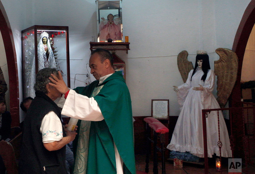 "In this Feb. 19, 2017 photo, Juan Carlos Avila blesses a devotee of the Death Saint at Mercy Church on the edge of Mexico City's Tepito neighborhood. Avila, who says he is a Catholic priest but is not listed among the archdiocese's priests, is a devotee of ""La Santa Muerte"" and says followers continue to grow. (AP Photo/Marco Ugarte)"