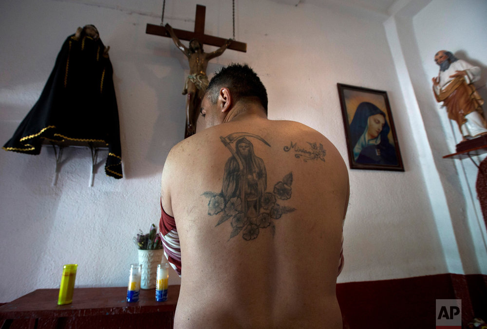 "In this Feb. 19, 2017 photo, Death Saint devotee Francisco Rodriguez shows his tattoo of the popular saint inside Mercy Church on the edge of Mexico City's Tepito neighborhood. To devotees, ""Santa Muerte"" is associated with healing, protection, financial well-being, and ensuring a path to the afterlife. (AP Photo/Marco Ugarte)"