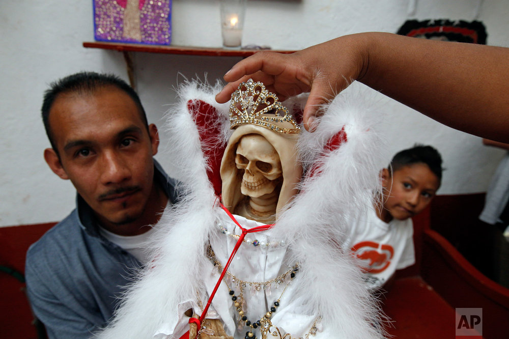 In this Feb. 19, 2017 photo, a man holds a Death Saint statue as his wife places a crown and his son looks on, at Mercy Church on the edge of Mexico City's Tepito neighborhood. To followers, she's known as the Death Saint, the White Girl, the Skinny One, or just Sister - and a life-transforming answer to their prayers. To the Vatican, though, she's an irritation seen as leading the faithful astray. (AP Photo/Marco Ugarte)