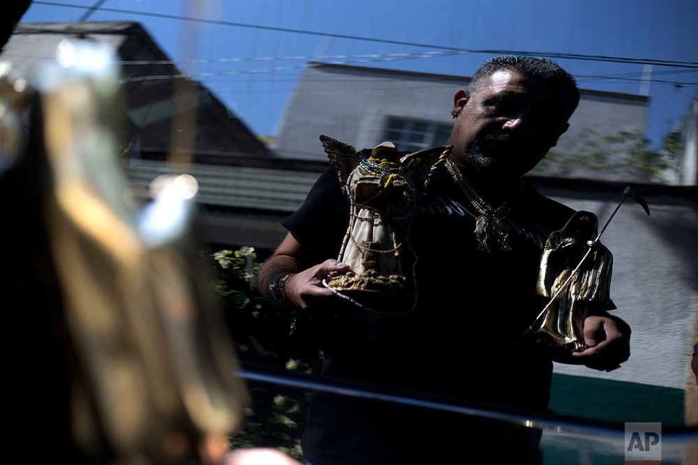 "In this March 1, 2017 photo, Manuel Zavala, a devotee of Death Saint or ""Santa Muerte,"" is reflected on a car window as he holds statues of the folk saint during a pilgrimage in Mexico City's Tepito neighborhood. Zavala credits the saint for turning him around: ""Thanks to a person I love a lot, my White Girl, my life has changed and now I'm not the second-rate guy I was before."" (AP Photo/Marco Ugarte)"