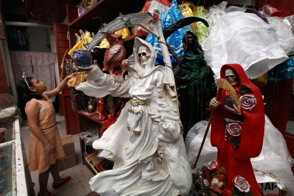 "In this Feb. 19, 2017 photo, a child arranges statues of the Death Saint at Mercy Church on the edge of Mexico City's Tepito neighborhood. Saint Death, or ""Santa Muerte,"" devotees say she has millions of followers and various names: the Death Saint, the White Girl, the Skinny One or just Sister. But she doesn't have her own religion, and her followers are Catholics. (AP Photo/Marco Ugarte)"