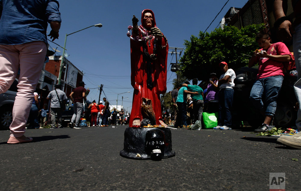 "In this March 1, 2017 photo, a Death Saint or ""Santa Muerte"" statuette stands in the middle of the road, placed there by its owner who waits for people to offer it things like food, tobacco and alcohol, in Mexico City's Tepito neighborhood. According to popular belief, ""Santa Muerte"" is very powerful and is reputed to grant many favors. (AP Photo/Marco Ugarte)"