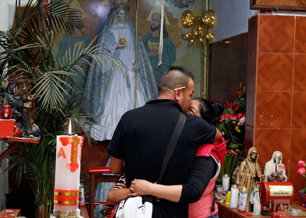 "In this Feb. 26, 2017 photo, devotees of the Death Saint or ""Santa Muerte"" embrace during a service at Mercy Church in Mexico City's Tepito neighborhood. Devotees believe the folk saint can protect against assaults, accidents, gun violence, and all types of violent death. (AP Photo/Marco Ugarte)"