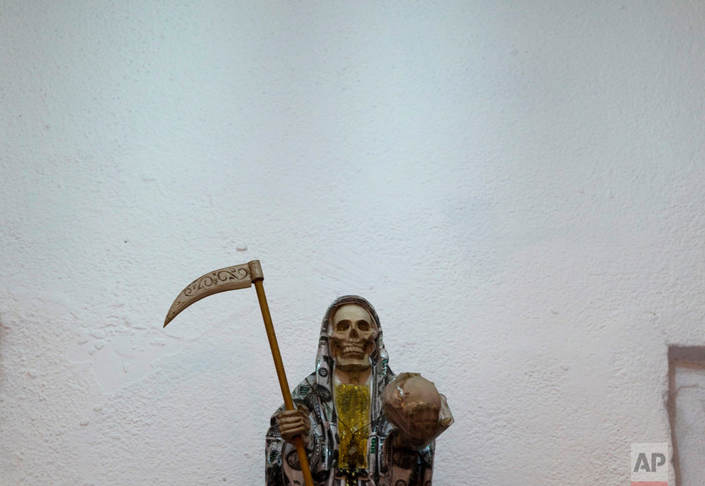 "In this Feb. 26, 2017 photo, a statue of the Death Saint or ""Santa Muerte"" wears a cloak of U.S. dollar bills inside Mercy Church on the edge of Mexico City's Tepito neighborhood. Usually the vestments of the folk saint are differently colored robes, but it is also common for her to be dressed as a bride or in nun's garments. (AP Photo/Marco Ugarte)"