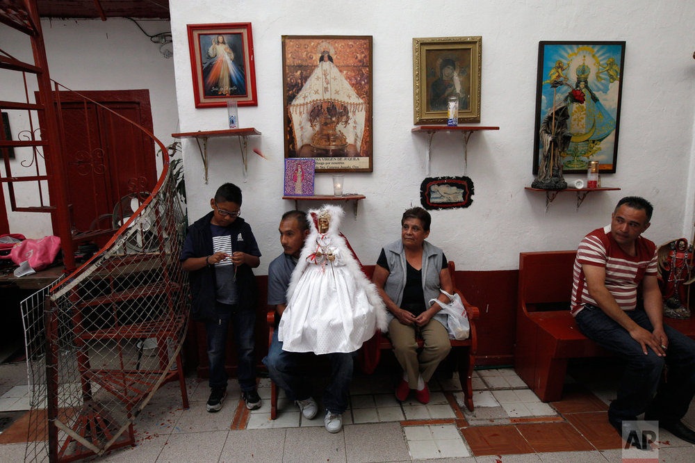 "In this Feb. 19, 2017 photo, a family of devotees to the Death Saint or ""Santa Muerte"" hold a statue of the folk saint in a white dress at Mercy Church on the edge of Mexico City's Tepito neighborhood. The colors of the saint's vestments are associated with the type of petitions made. (AP Photo/Marco Ugarte)"