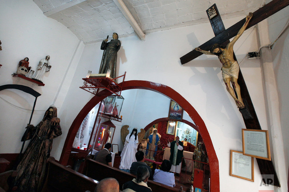 "In this Feb. 19, 2017 photo, Juan Carlos Avila Mercado leads a religious service, surrounded by images of local saints, Saint Death, Immaculate Conception, Saint Judas Thaddeus and the Virgin of Guadalupe, at Mercy Church in Mexico City. The Church located on the edge of the Tepito neighborhood is home to the cult of the Death Saint, or ""La Santa Muerte"" in Spanish, a female figure cloaked in black who carries a scythe, which the Roman Catholic Church rejects. (AP Photo/Marco Ugarte)"