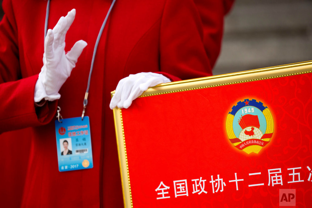 In this Friday, March 3, 2017 photo, a hospitality staff member holds a signboard with the logo of the Chinese People's Political Consultative Congress (CPPCC) as she directs delegates after the end of the opening session of the CPPCC at the Great Hall of the People in Beijing. (AP Photo/Mark Schiefelbein)