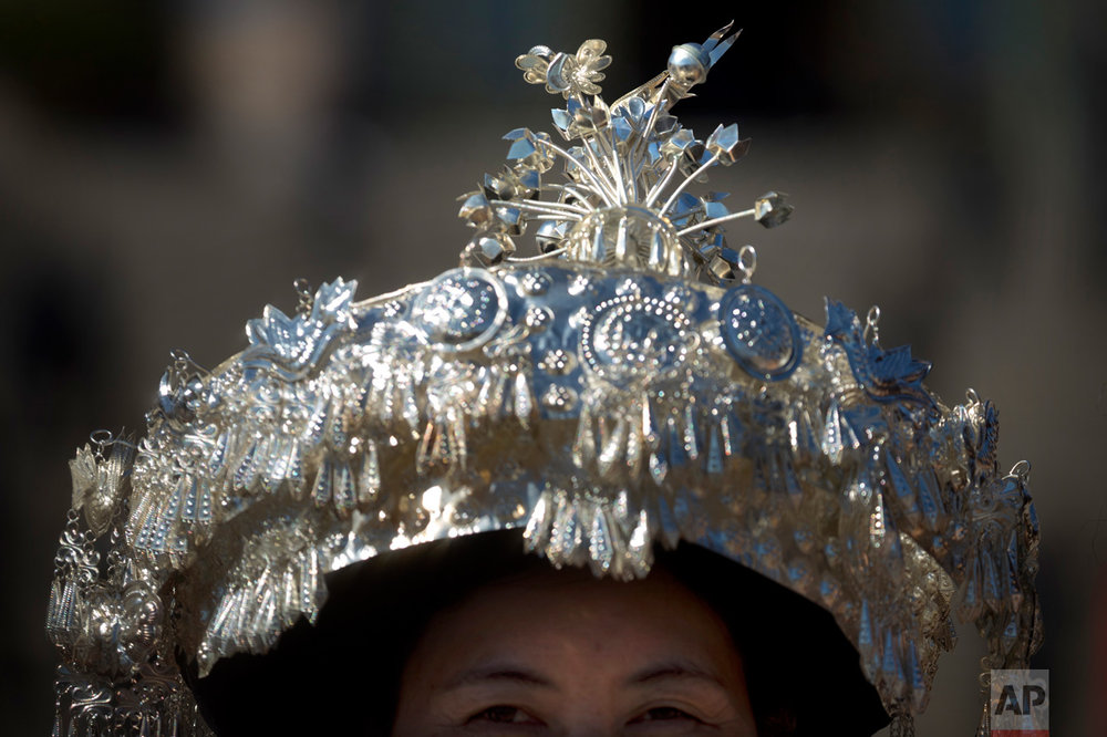 In this Sunday, March 12, 2017 photo, an ethnic minority delegate wears a hat topped with a silver bird as she leaves a plenary session of China's National People's Congress (NPC) at the Great Hall of the People in Beijing. (AP Photo/Mark Schiefelbein)