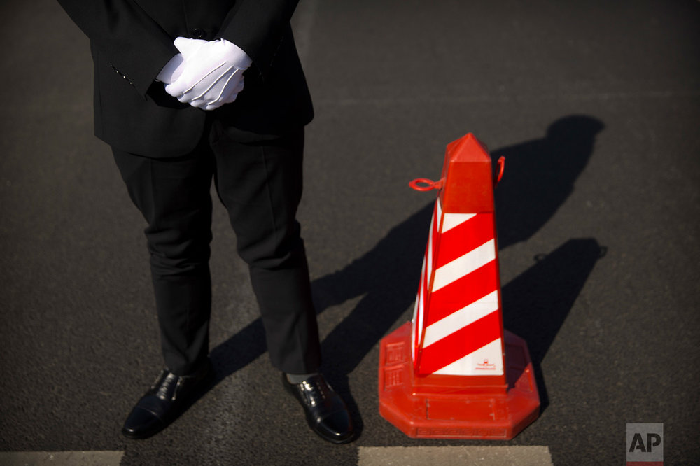 In this Wednesday, March 8, 2017 photo, a security official stands next to a traffic cone as he guards a crosswalk outside of the Great Hall of the People before a plenary session of China's National People's Congress (NPC) in Beijing. (AP Photo/Mark Schiefelbein)