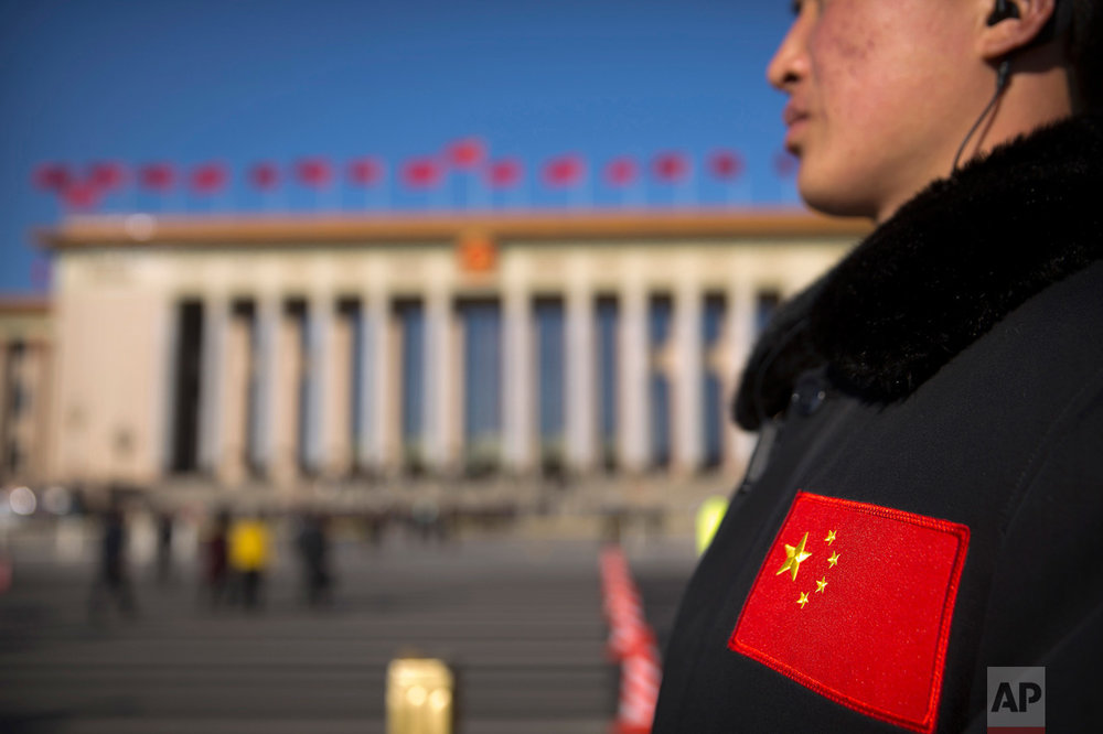 In this Sunday, March 12, 2017 photo, a security official with a Chinese flag patch on his jacket stands guard outside of the Great Hall of the People before a plenary session of the National People's Congress (NPC) in Beijing. (AP Photo/Mark Schiefelbein)