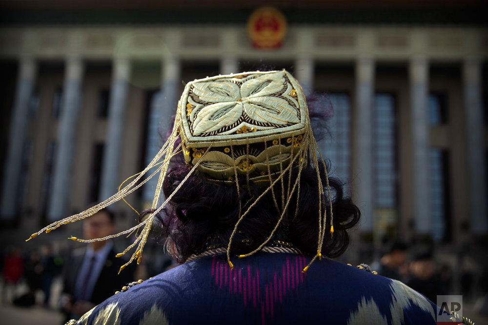 In this Saturday, March 11, 2017 photo, tassels on the hat of an ethnic minority delegate blow in the breeze as she arrives for a plenary session of the Chinese People's Political Consultative Congress (CPPCC) at the Great Hall of the People in Beijing. (AP Photo/Mark Schiefelbein)
