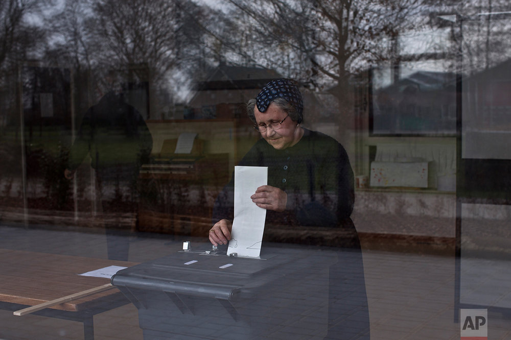 An elderly woman casts her ballot for the Dutch general elections at a polling station set up in a school in Staphorst, Netherlands, Wednesday, March 15, 2017.  (AP Photo/Muhammed Muheisen)