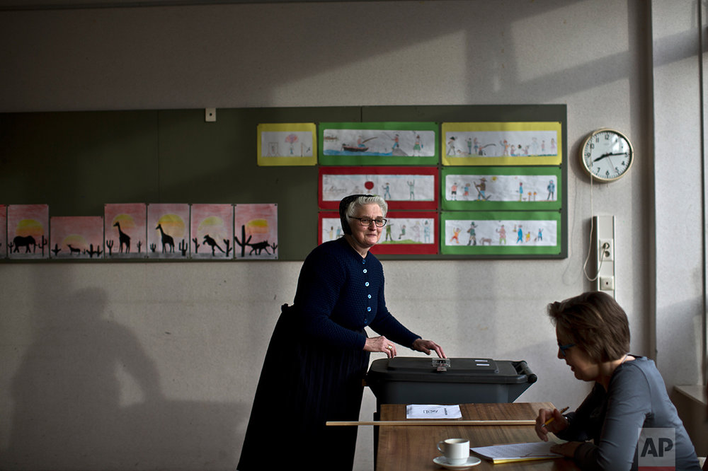 A woman casts her ballot for Dutch general elections at a polling station set up in a school in Staphorst, Netherlands, Wednesday, March 15, 2017. (AP Photo/Muhammed Muheisen)
