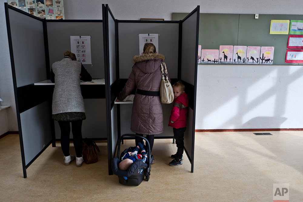 A boy stands next to his mother as she fills out her ballot prior to casting her vote for the Dutch general elections at a polling station set up in a school in Staphorst, Netherlands, Wednesday, March 15, 2017. (AP Photo/Muhammed Muheisen)