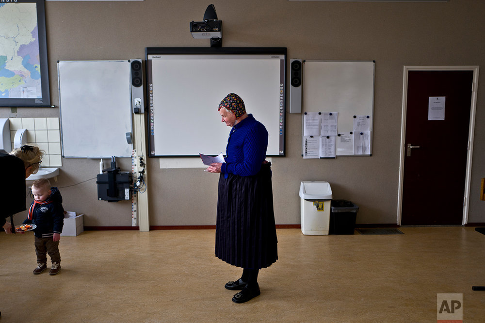 An elderly woman waits her turn to receive her ballot prior to casting her vote for Dutch general elections at a polling station set up in a school in Staphorst, Netherlands, Wednesday, March 15, 2017.  (AP Photo/Muhammed Muheisen)