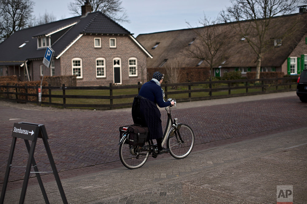 An elderly woman rides her bicycle after casting her ballot for the Dutch general elections at a polling station set up in a cafe in Staphorst, Netherlands, Wednesday, March 15, 2017. (AP Photo/Muhammed Muheisen)