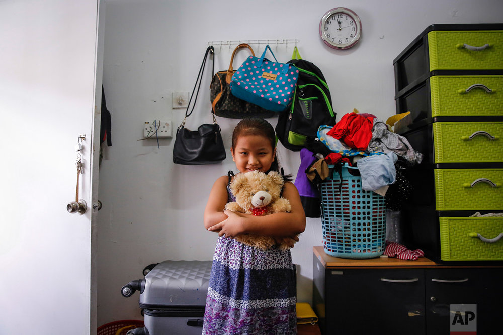 "In this Saturday, March 11, 2017, photo, Burmese Christian refugee Sarah,10, poses for a photograph with her favorite teddy bear in Kuala Lumpur, Malaysia. ""I'd like to take them all, she said. ""This is my favorite bear. This is the bear I would take,"" she said. Refugees live for years out of suitcases, many envisioning their future in America. They own very little and will bring even less, but everyone has at least one precious item that they were planning to bring to the place they call their ""fatherland."" (AP Photo/Joshua Paul)"