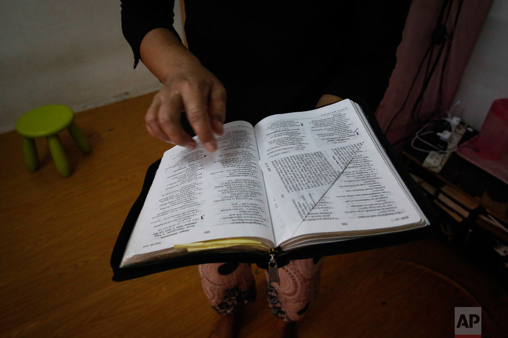 "In this Saturday, March 11, 2017, photo, Tin, a Burmese Christian refugee, leafs through her Bible to share her favorite scripture during an interview in Kuala Lumpur, Malaysia. ""As refugees we have nothing,"" Tin said. ""But everywhere I go I will bring my Bible, nothing else."" Refugees live for years out of suitcases, many envisioning their future in America. They own very little and will bring even less, but everyone has at least one precious item that they were planning to bring to the place they call their ""fatherland."" (AP Photo/Joshua Paul)"