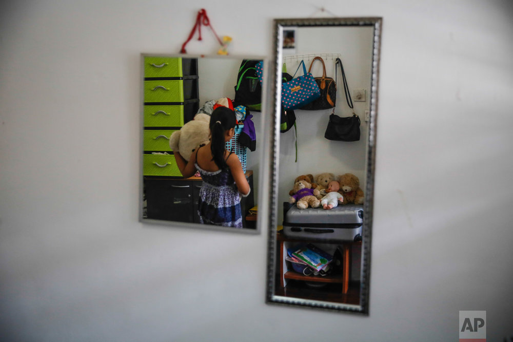 "In this Saturday, March 11, 2017, photo, Sarah, 10, a Burmese Christian refugee, is reflected in a mirror as she arranges her teddy bears in Kuala Lumpur, Malaysia. ""I'd like to take them all,"" she said. ""This is my favorite bear. This is the bear I would take."" Refugees live for years out of suitcases, many envisioning their future in America. They own very little and will bring even less, but everyone has at least one precious item that they were planning to bring to the place they call their ""fatherland."" (AP Photo/Joshua Paul)"