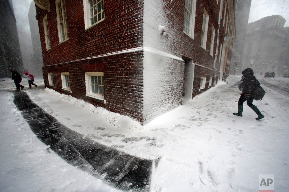 People walk in the wind-driven snow during a winter storm in Boston on Tuesday, March 14, 2017. The powerful nor'easter that paralyzed much of the Washington-to-Boston corridor Tuesday fell short of the predicted snowfall in many areas. (AP Photo/Michael Dwyer)