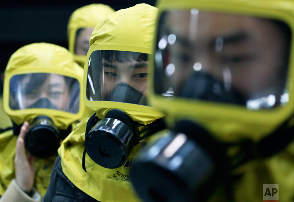 South Korean government officials wearing gas masks attend a civil defense drill against a possible North Korea's chemical attack at their office in Seoul, South Korea, Wednesday, March 15, 2017. A nationwide civil defense drill took place Wednesday preparing for possible terror, natural disaster or sudden air attack by North Korea. (AP Photo/Ahn Young-joon)