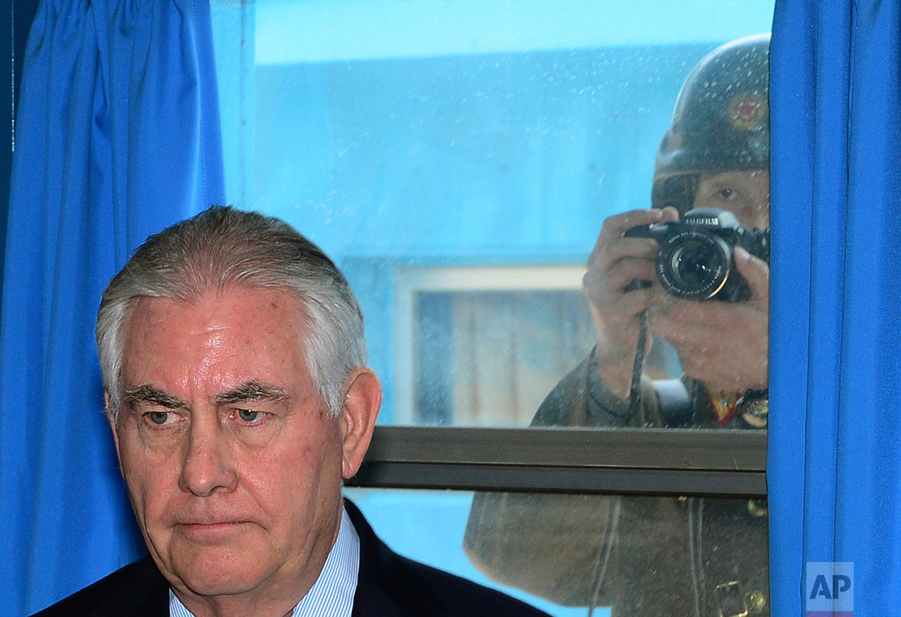 A North Korean soldier, right, tries to take a photograph through a window while U.S. Secretary of State Rex Tillerson visits the U.N. Command Military Armistice Commission meeting room Friday, March 17, 2017, in the border village of Panmunjom, which has separated South and North Korea since the Korean War. Tillerson on Friday visited the world's most heavily armed border, greeting U.S. soldiers on guard near the tense buffer zone between rivals North and South Korea. (Korea Pool/Yonhap via AP)