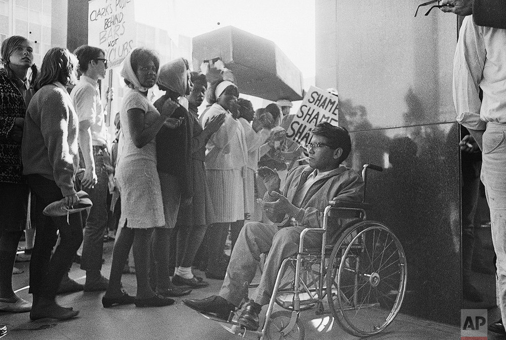 Andrew McDonald II, a San Jose State college student from Hayward, claps as San Jose marchers parade at the Federal Building in San Francisco on March 14, 1965 during Selma, Alabama protest demonstration. The San Jose group walked the 45 miles to San Francisco in three days. McDonald said he wheeled most of the way. (AP Photo)