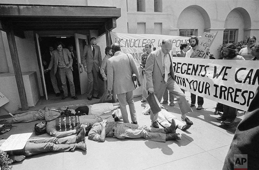 More than 100 students and other anti-nuclear demonstrators protest outside the UC Regent's office in San Francisco after the Regents voted 7-15 to maintain ties with the Los Alamos, N.M., nuclear laboratory that has developed every major nuclear weapon, July 20, 1979. Several demonstrators lay on the ground to simulate death from nuclear war, forcing several regents to climb over them. (AP Photo/Olsen)