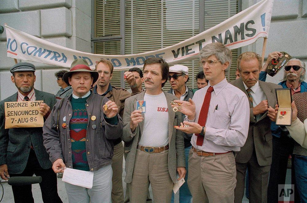 Veterans, holding their medals they received from three wars, stand beneath a banner in San Francisco, Calif., Aug. 7, 1986, protesting America's policies in Central America. More than 20 veterans handed in their Purple Hearts, Bronze Stars and other medals in a ceremony to protest the escalating, U.S. role in Central America. (AP Photo/Jim Gerberich)
