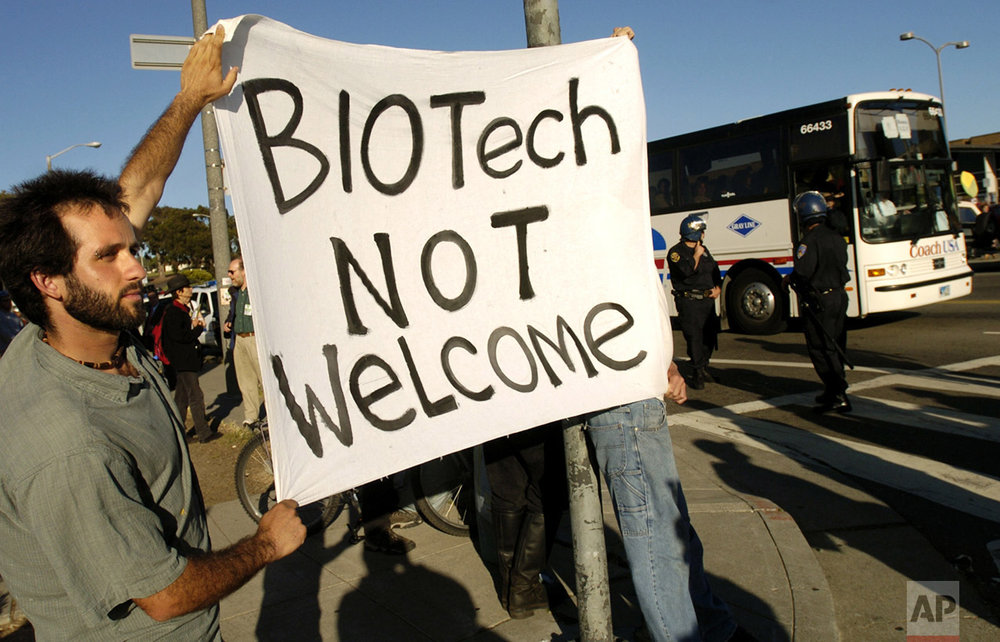 In this June 6, 2004 photo, Ryan Silva holds a protest banner as a busload of BIO 2004 conference attendees arrive for an opening night reception in San Francisco. (AP Photo/Noah Berger)