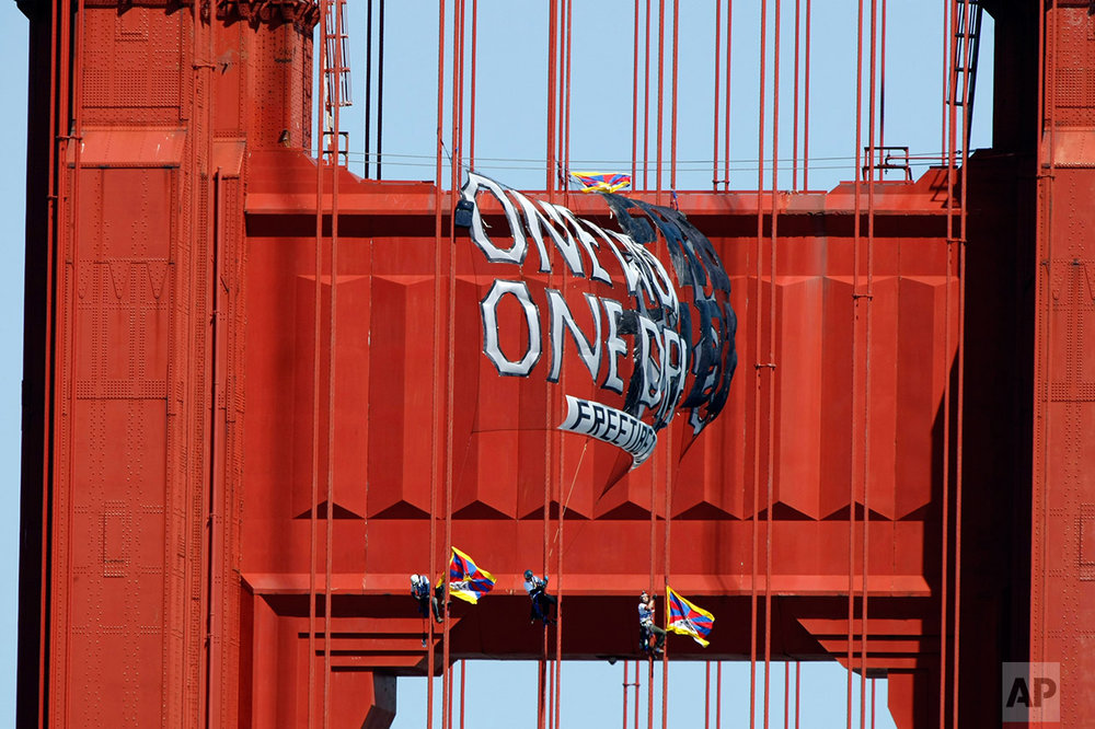 Three members of the Students for a Free Tibet hang a banner from the Golden Gate Bridge to protest China's human rights record and the impending arrival of the Olympic torch in San Francisco on Monday, April 7, 2008. (AP Photo/Jakub Mosur)