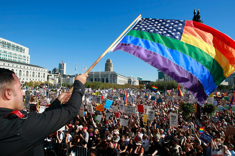 In this Nov. 15, 2008 photo, Alexander Sanchez waves a rainbow-colored U.S. flag in front of a large crowd of supporters of same-sex marriage in front of City Hall in San Francisco. (AP Photo/Darryl Bush)
