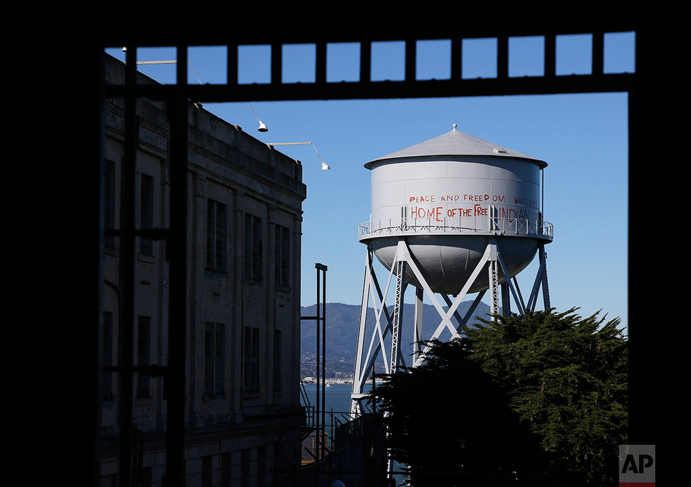 "This Jan. 14, 2013 photo shows a restored water tower with graffiti, shown through an entryway to the main cell house on Alcatraz Island in San Francisco. The writing, which is on a roughly 10-story-tall water tower on the island's northern end, reads ""Peace and Freedom Welcome Home of the Free Indian Land"" in red capital letters up to 5 feet high. (AP Photo/Eric Risberg)"