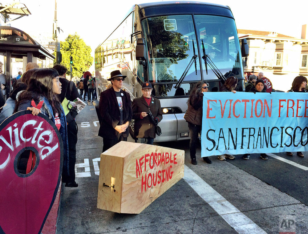 In this Dec. 20, 2013 photo, anti-gentrification protesters temporarily block a shuttle bus full of tech workers at a Mission District public bus stop in San Francisco. (Kurtis Alexander/San Francisco Chronicle via AP)
