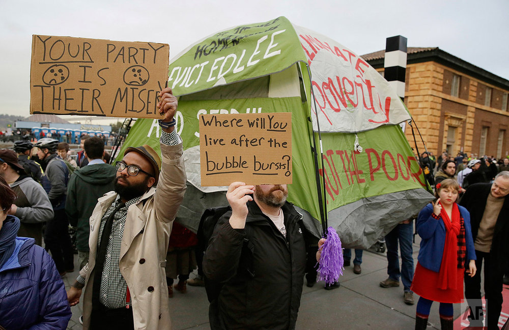 In this Feb. 3, 2016 photo, people hold up signs and a tent during a protest to demand city officials do more to help homeless people outside Super Bowl City, a weeklong football theme park near the Ferry Building in San Francisco. (AP Photo/Eric Risberg)