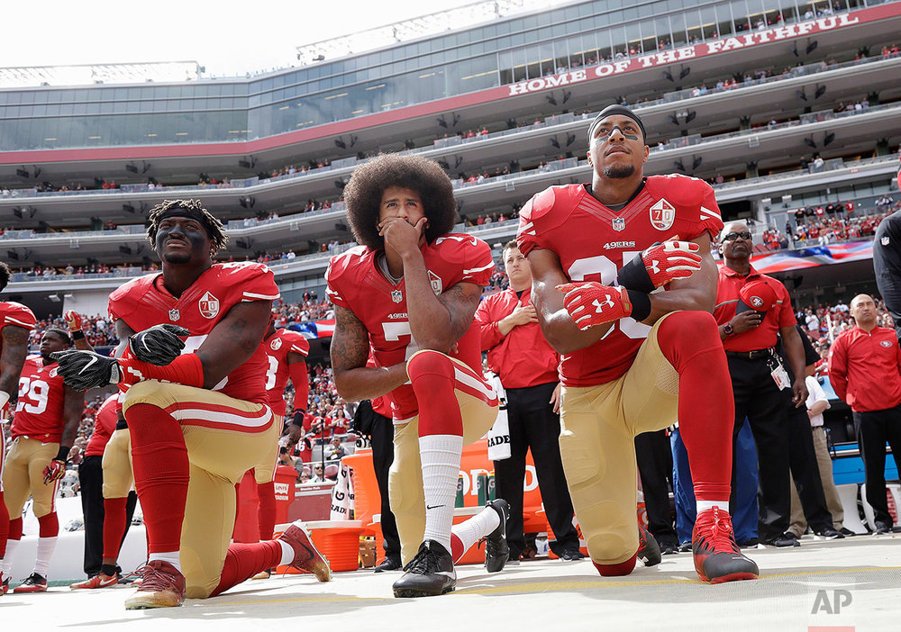 In this Oct. 2, 2016 photo, from left, San Francisco 49ers outside linebacker Eli Harold, quarterback Colin Kaepernick and safety Eric Reid kneel in protest during the national anthem before an NFL football game against the Dallas Cowboys in Santa Clara, Calif. (AP Photo/Marcio Jose Sanchez)