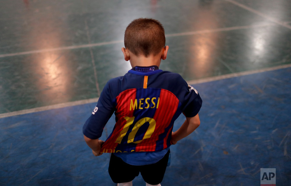 In this Nov. 11, 2016 photo, Benjamin Palandella puts on his Barcelona jersey adorned with Messi's number 10 after a training game at the youth soccer academy Club Social Parque in a working class neighborhood of Buenos Aires, Argentina. After the training game, Benjamin continued to kick the ball even after the other kids had gone home. (AP Photo/Natacha Pisarenko)
