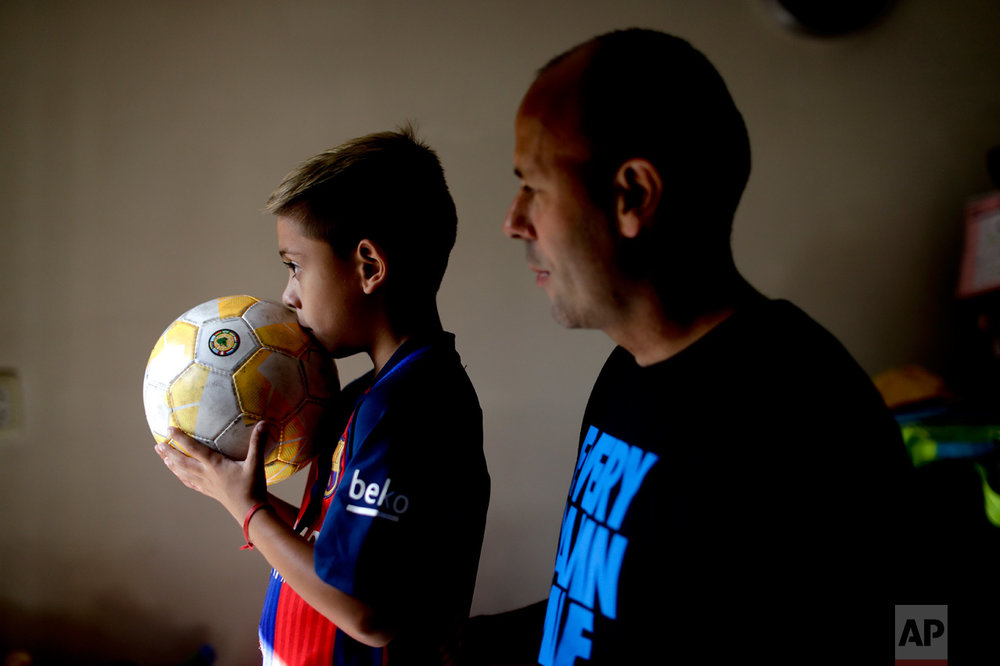 "In this Jan. 25, 2017 photo, young soccer player Benjamin Palandella stands with his father Gaston at their home in Buenos Aires, Argentina. ""Benjamin is very shy, but he transforms himself on the field,"" his father said. (AP Photo/Natacha Pisarenko)"