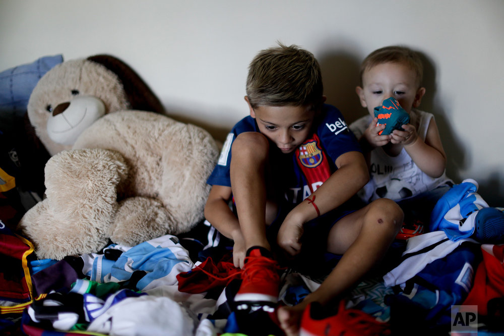 "In this Jan. 25, 2017 photo, Benjamin Palandella puts on his soccer shoes as he sits with his little brother Bautista Lionel and his stuffed toys on his bed in Buenos Aires, Argentina. ""I want to be like Messi and play for Barcelona,"" said Palandella. He likes how the Barcelona star ""steps"" on the ball, scores and shoots free kicks. (AP Photo/Natacha Pisarenko)"