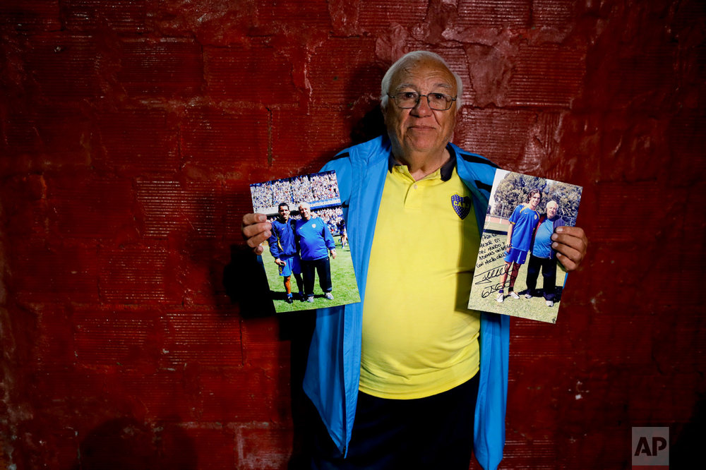 In this Nov. 11, 2016 photo, Ramon Maddoni, head scout at youth soccer academy Club Social Parque and at the Boca Juniors club children's division, poses with photos of himself with professional players Carlos Tevez and Fernando Gago in Buenos Aires, Argentina. Maddoni recalls how he promised Tevez that he'd be a world-class striker long before he became a top goal scorer for clubs in England and Italy. (AP Photo/Natacha Pisarenko)