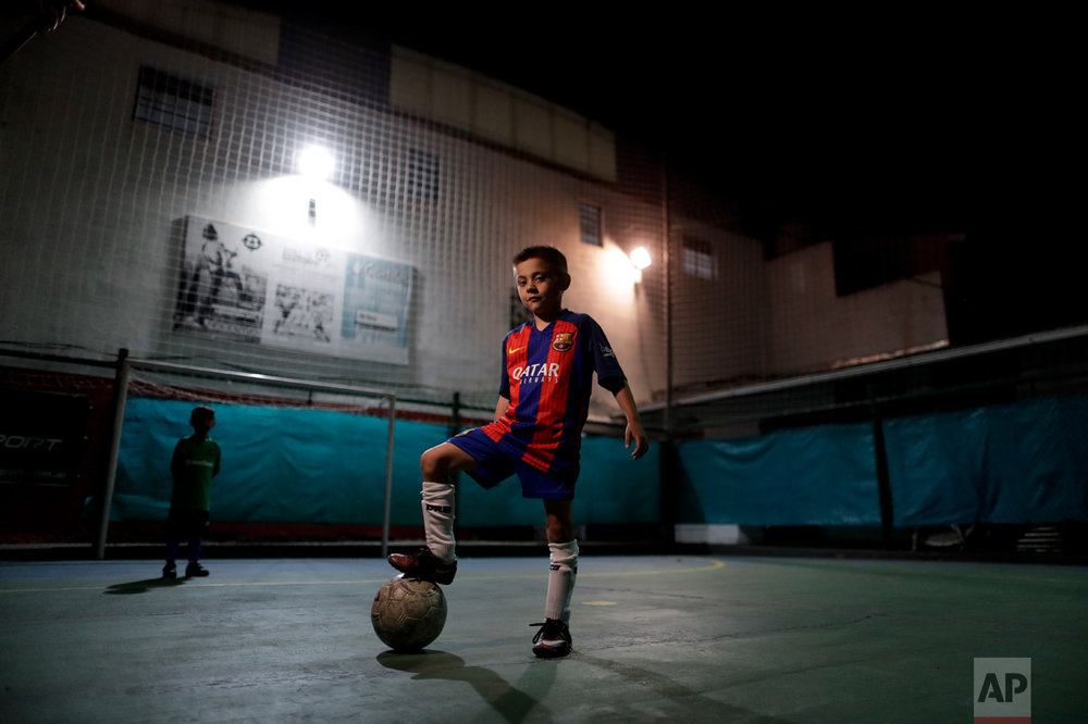 "In this Nov. 11, 2016 photo, Benjamin Palandella poses for a portrait wearing his Barcelona shirt after a training session in Buenos Aires, Argentina. Palandella's coach Ramon Maddoni said ""Benjamin is different from the group. He can pass with his back turned, he uses both legs."" (AP Photo/Natacha Pisarenko)"