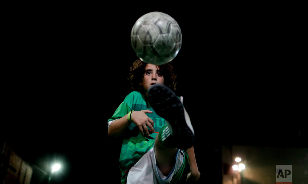 "In this Nov. 11, 2016 photo, Thiago ""Coco"" Perugini controls the ball in Buenos Aires, Argentina. Perugini is one of the top young players at the youth soccer academy Club Social Parque, and has been invited to play with kids two years older than him. (AP Photo/Natacha Pisarenko)"