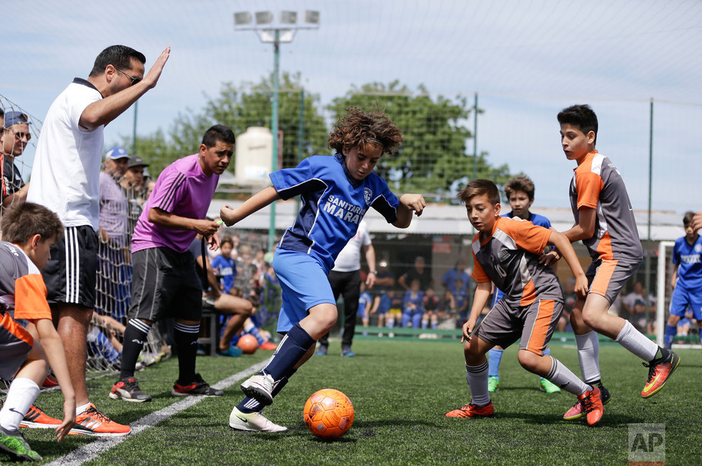 "In this Nov. 19, 2016 photo, Thiago ""Coco"" Perugini controls the ball during a youth league game on the outskirts of in Buenos Aires, Argentina. ""The day that he doesn't want to play anymore, it all ends right here. He has to be a good person and study and he has the support of his parents,"" said Thiago's dad, Diego Perugini, a former lower division soccer player who is a coach at Parque. (AP Photo/Natacha Pisarenko)"